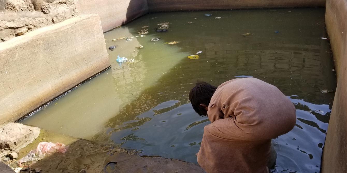 طفل يحاول جلب الماء لعائلته من مستنقع