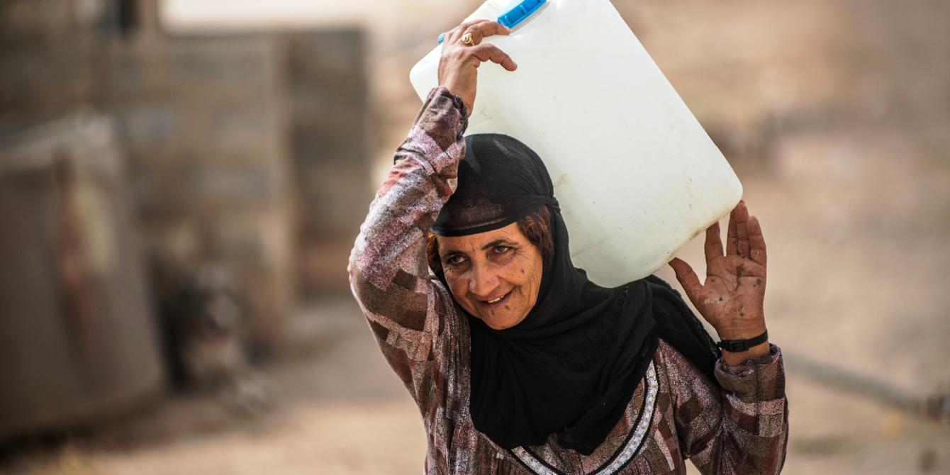 إمرأة تجمع الماء في مخيم للنازحين في العراق