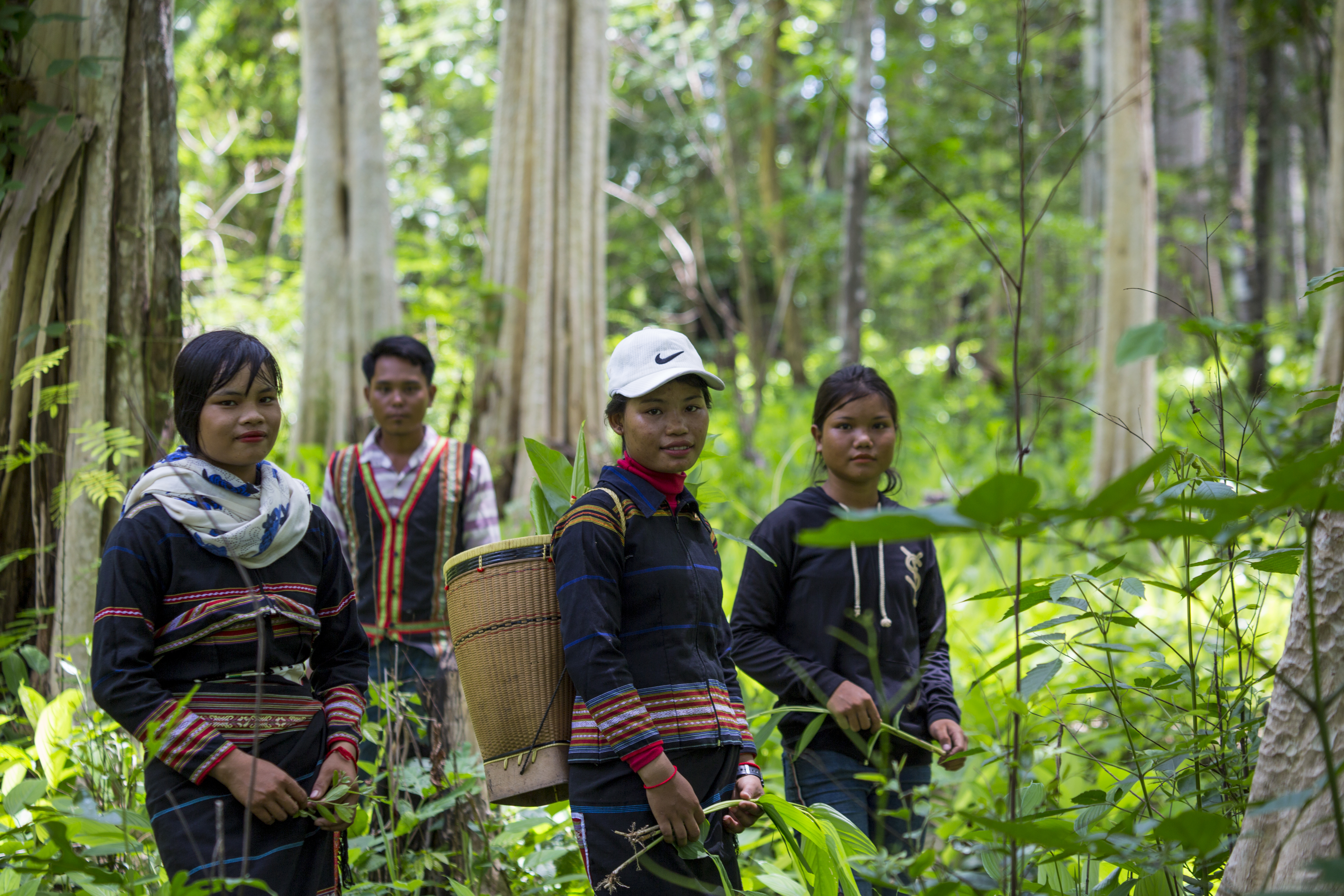 Sav Leat stands behind the young women in the community forest of Pa Tang village while they are posting for a picture to share on their facebook. Photo by Savann Oeurm/Oxfam