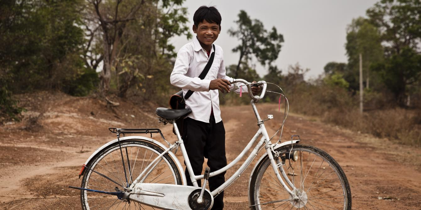 Mab Oeuy, 15, has been a member of a Saving for Change group for two years. He saved up some money, and borrowed enough from his group to buy a bicycle