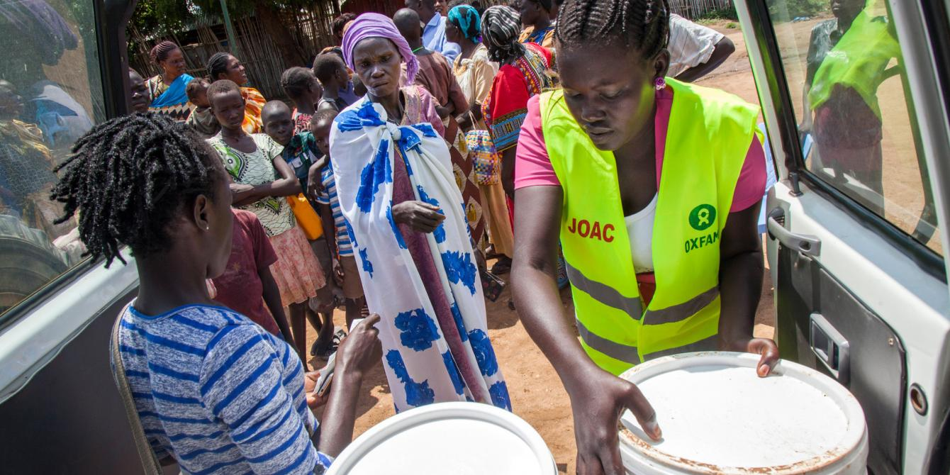 Oxfam staff distributing water treatment kits in Juba, South Sudan. Albert Gonzalez Farran / Oxfam