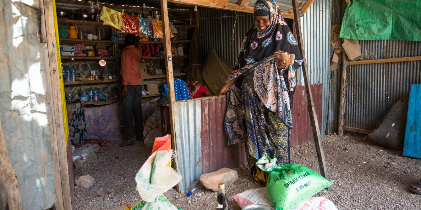 A woman stands outside a shop in eastern Somaliland. Allan Gichigi/Oxfam