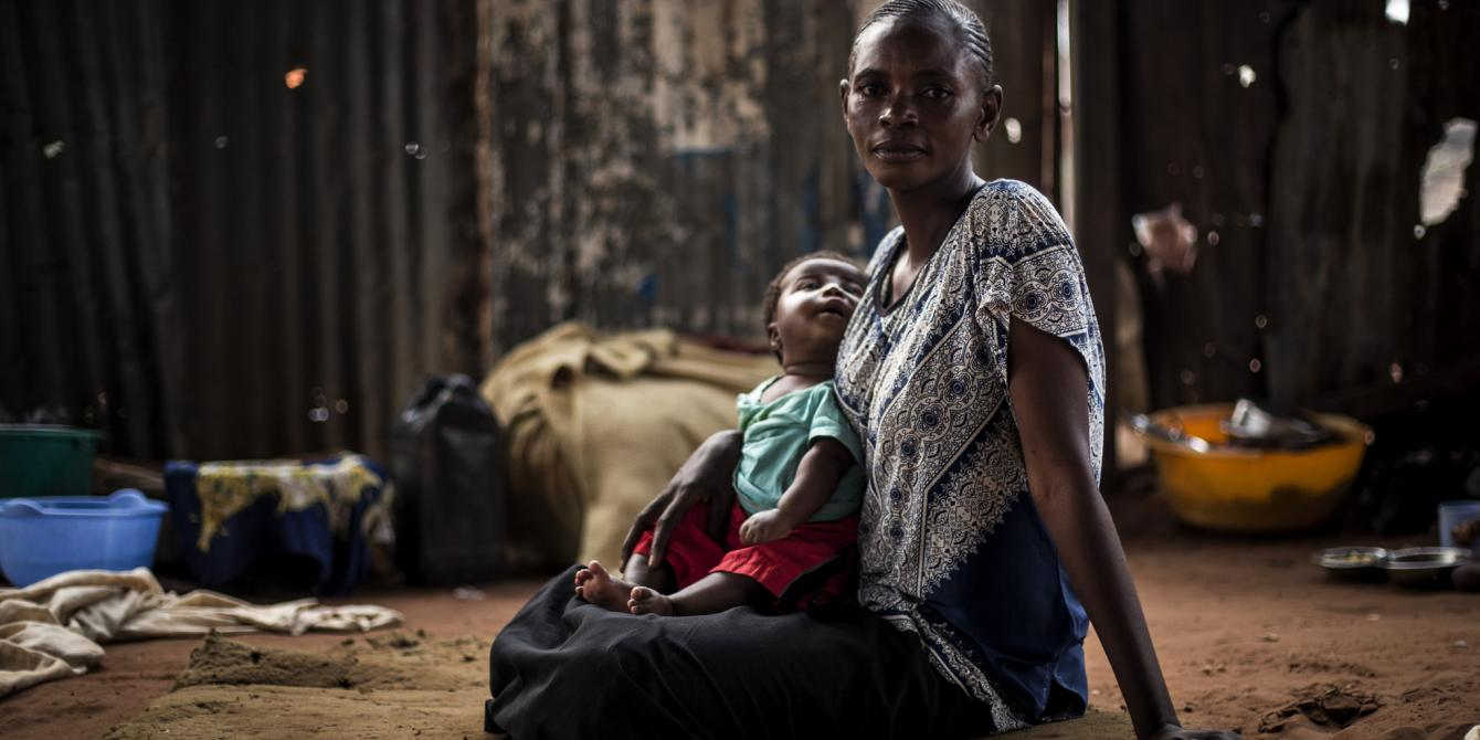 Berte sits with her child inside a church in Kasai province, eastern DRC. John Wessels / Oxfam