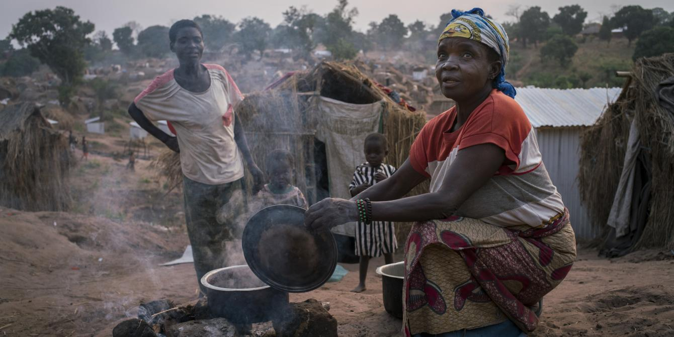 A woman prepares dinner as night falls on Kalunga IDP camp. Kalemie, Tanganyika, Democratic Republic of the Congo. Diana Zeyneb Alhindawi/Oxfam