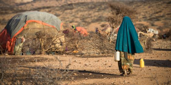 A woman walks through a settlement for displaced families in Somaliland. Allan Gichigi/Oxfam