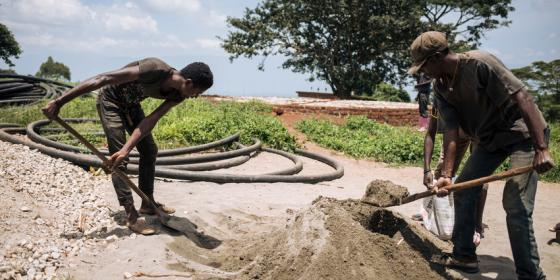 Two Oxfam workers prepare concrete to build a platform to host a water tank in Fizi territory. Alexis Huguet/Oxfam Novib