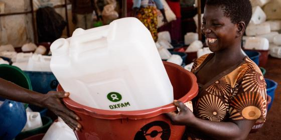 A Burundian refugee receives a bucket and jerry cans at an Oxfam distribution in Nduta camp, Tanzania. Amy Christian/Oxfam
