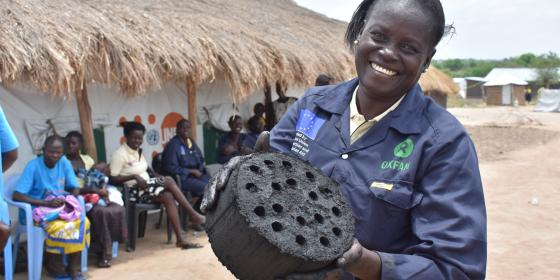 Dawa Deborah of the Loketa Women's Group in Rhino refugee settlement shows off one of the briquettes made by the group. Credit: Oxfam