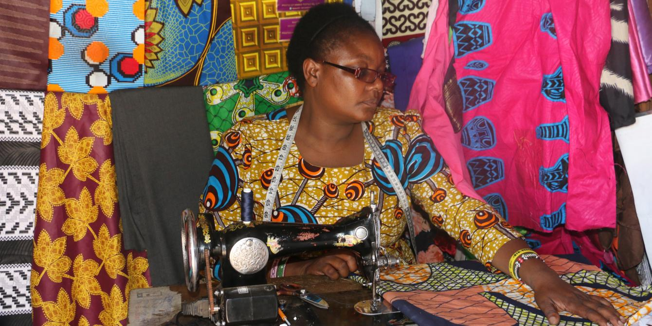 Peris sewing a dress for a customer.