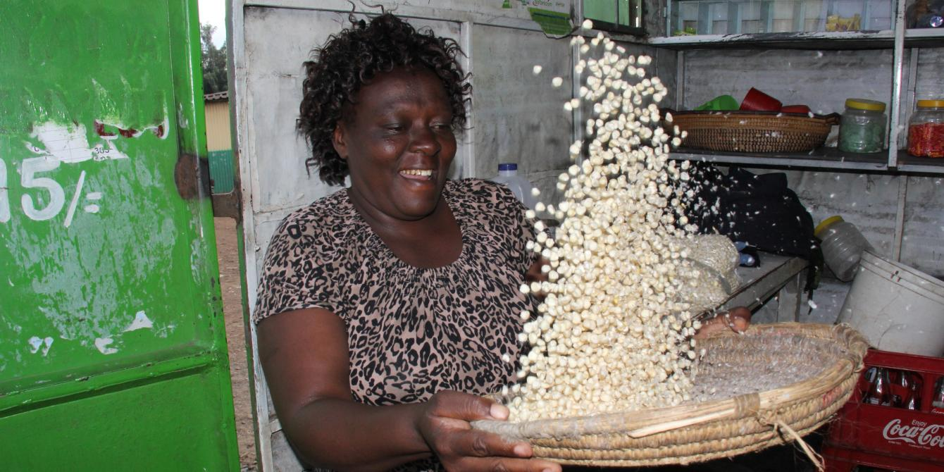 Small scale trader in Kibera market in Nairobi cleaning maize grains for sale in her small kiosk. Photo Credit: Benson Guantai
