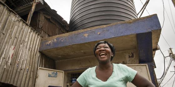 Clarice Akinyi, 35, Domestic Worker by a water tank in Mathare Ward, Mashimoni Village, Nairobi, Kenya. Photo Credit: Katie G. Nelson/Oxfam