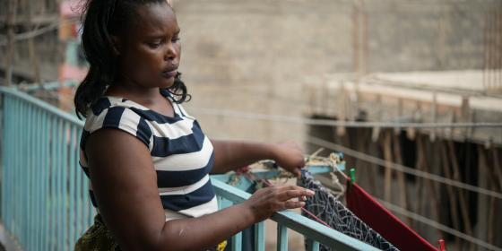 Domestic worker Elizabeth Wayua, 31, hangs clothes on the balcony outside her employer's house in Pipeline, Embakasi, Nairobi, Kenya. Photo Credit: Allan Gichigi