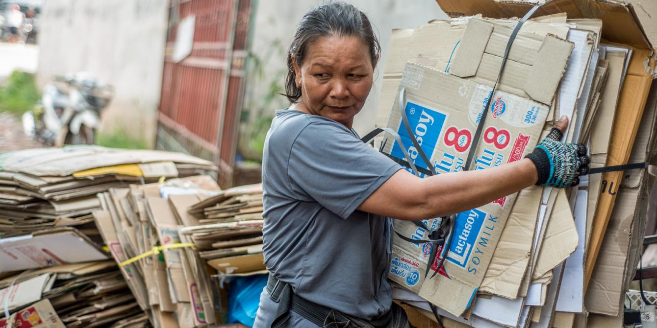 A Lao female informal worker carries a stack of old cardboard boxes for recycling