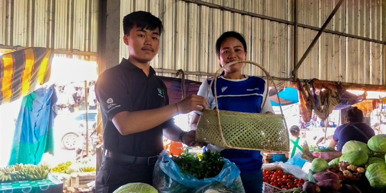 A student from the National University of Laos hand a bamboo basket to a wet market vendor
