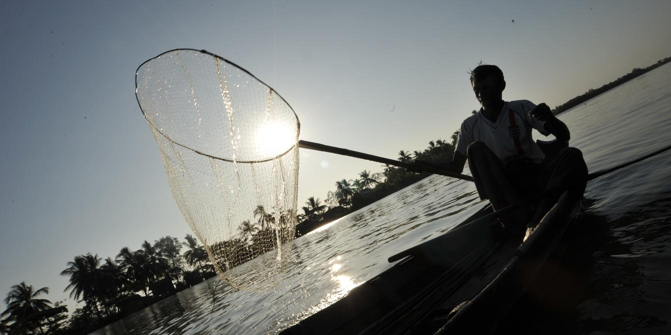 Fisher folk in the river with small fishing gear on his boat during sun set. This is the area where Oxfam works to support small scale fisher folks to aware their rights and claim for it. Photo by: Kaung Htet/Oxfam
