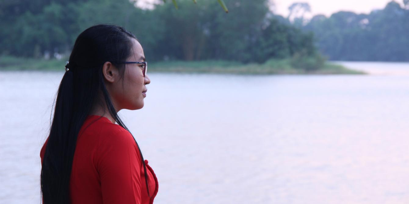Thet Htar Aung in red colour dress, is Looking at the water infront of her