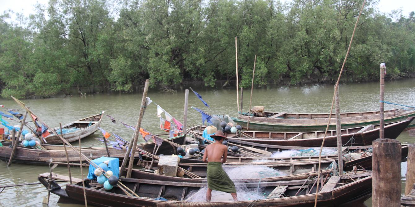 A man working on the boats in the river to go for fishing. Photo by: Oxfam