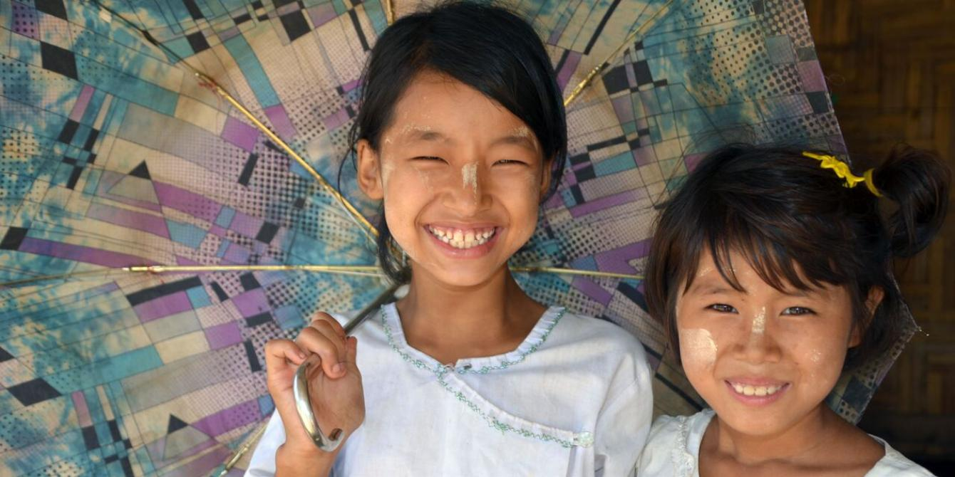 Two shool girls are smiling under their umbrella, in Kachin IDPs camp. Photo by: Dustin Barter/ Oxfam