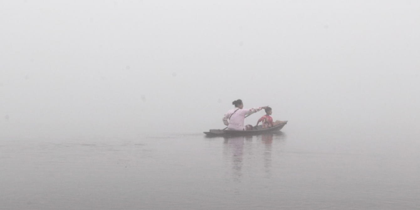 A boat carrying woman and child in the river.