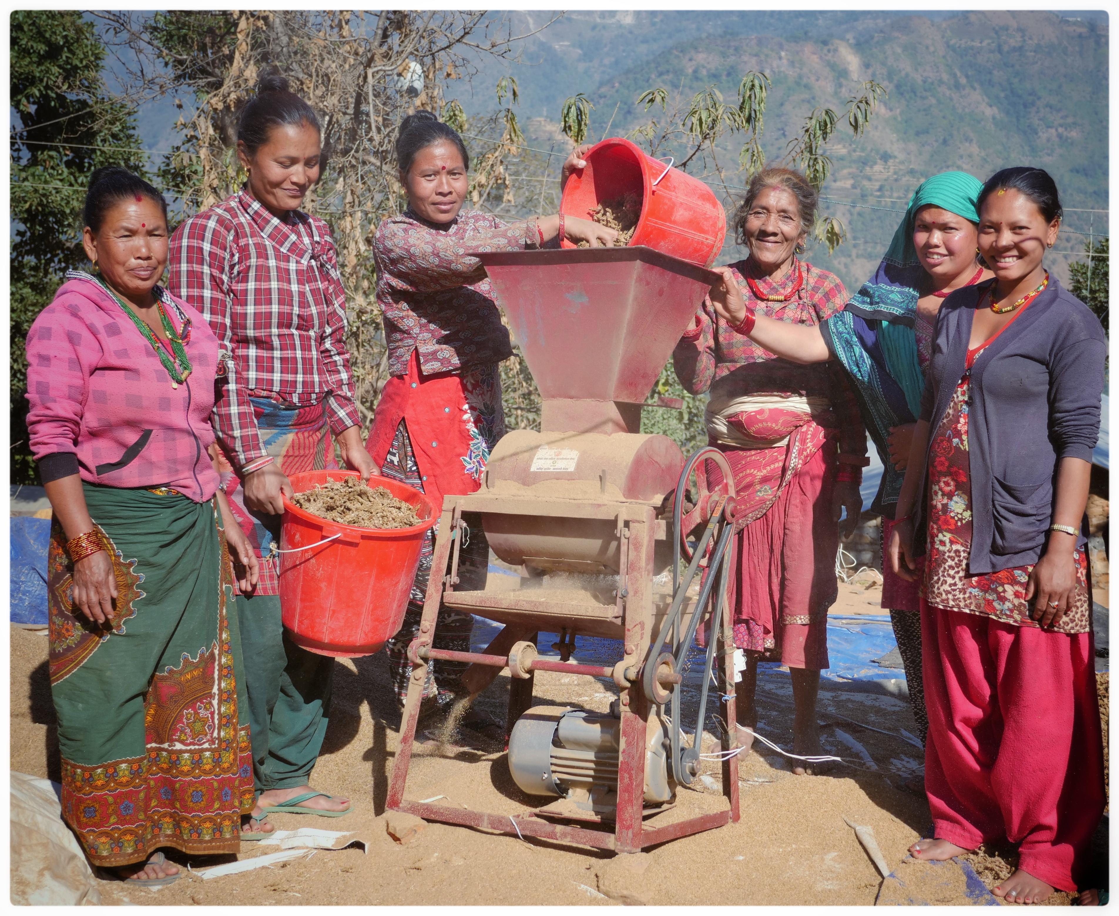 Women using a grain huller in Nepal