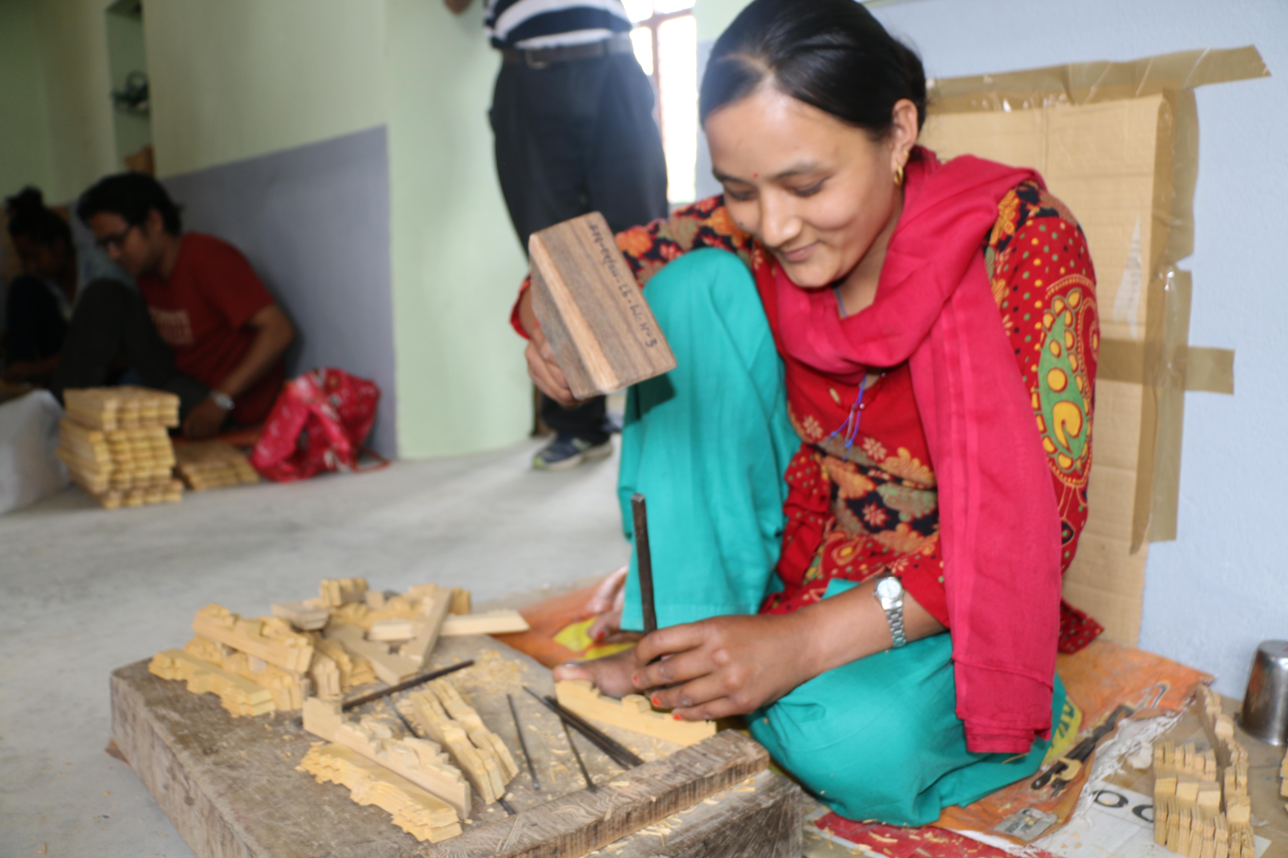 Shovita Shakya carving a wooden frame