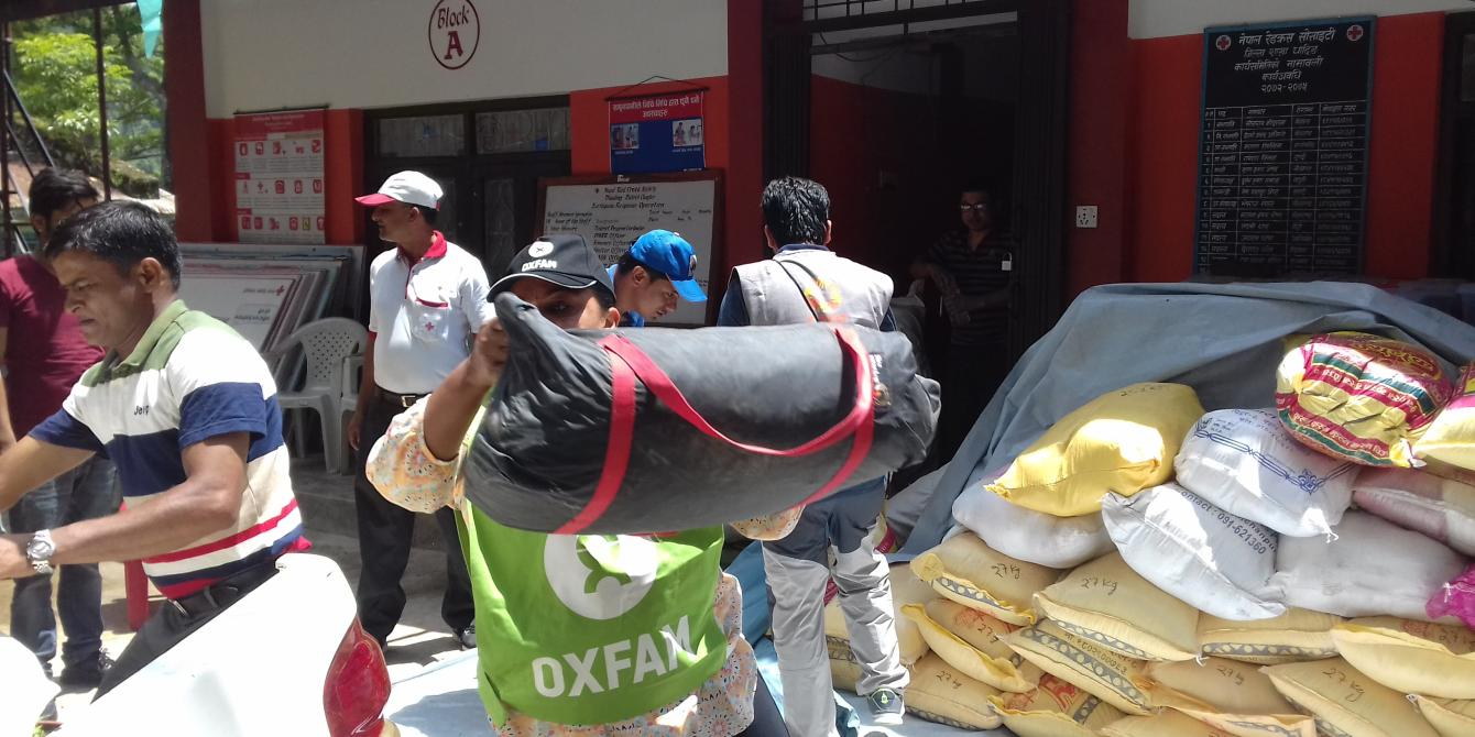 Oxfam staff carrying relief items