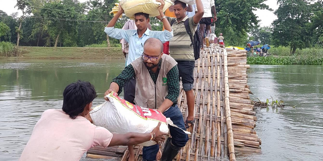 Oxfam staff handing food supplies to the people affected by 2017 floods in Sarlahi district. Photo credit: BWSN