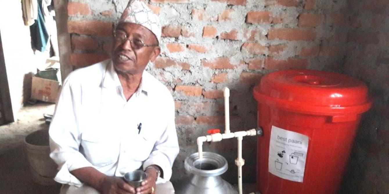 Harka Bahadur Ghimire holding a glass of filtered water. Photo by: Oxfam