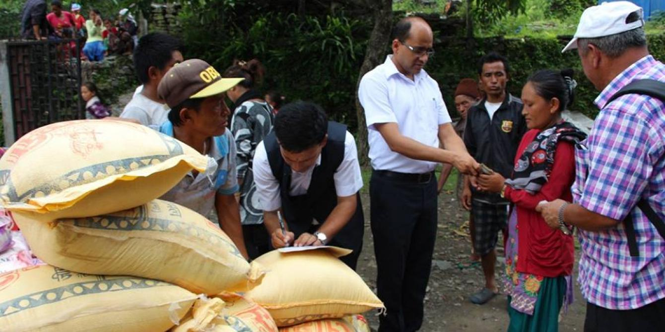 Dhading's CDO handing cash support to the affected people