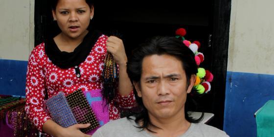 A man displaying beads jewellery he made