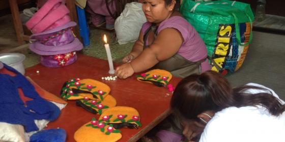 A woman making bag from felt
