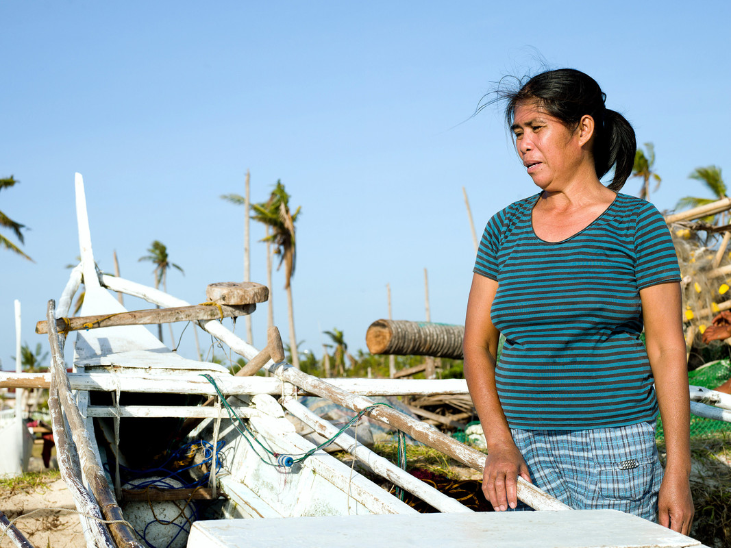 Fish Saleswoman Imelda Esgana (47) stands next to a fishing boat in Talisay, Bantayan. (Photo: Tessa Bunney)
