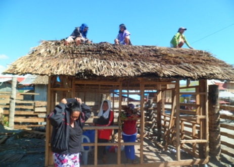 Women carpenters thatching roof of wooden house in Leyte (Farhana Hafiz/ Oxfam)