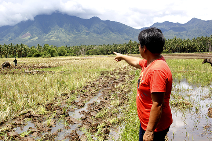 Former community leader Teresita Deles shows the rice field, where the bodies of eight people were found during the onslaught of Tropical Storm Urduja. Photo: Genevive Estacaan / Oxfam