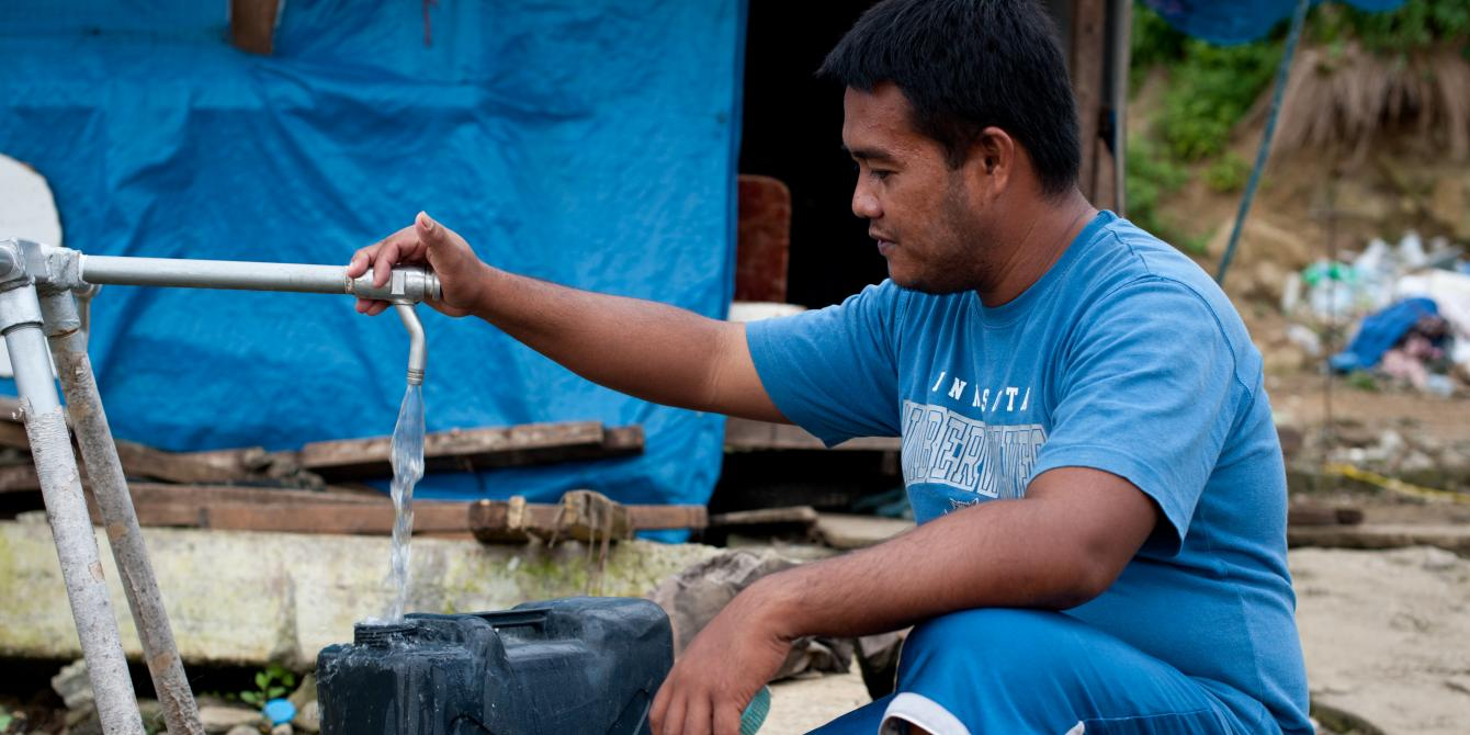 Christopher Acosta (27) uses an Oxfam tap stand in Anibong, Tacloban. (Photo: Eleanor Farmer/Oxfam)
