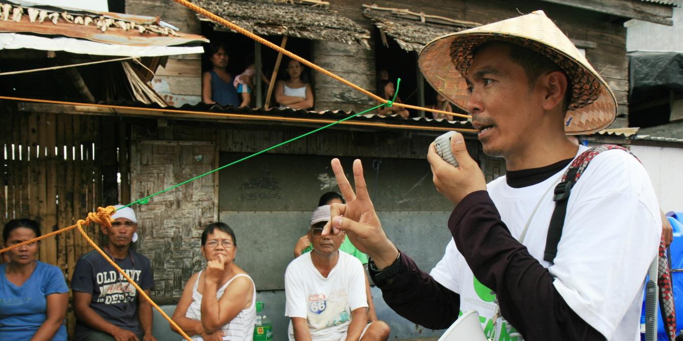 (HSP) Public Health Promoter. Making announcement at distribution for hygiene and water kits at Giporlos, Eastern Samar. (Photo: Jane Beesley/Oxfam)