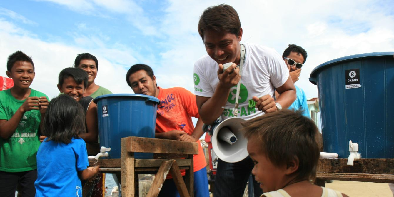 Christoper 'Toper' Cabalhiw (right), a local volunteer working with Oxfam as a Public Health Promoter, organising a relay hand washing race between two teams of children. Oxfam public health promotion activity aimed at encouraging children to understand why and how to wash their hands and use the latrines.(Photo:Jane Beesley/Oxfam)