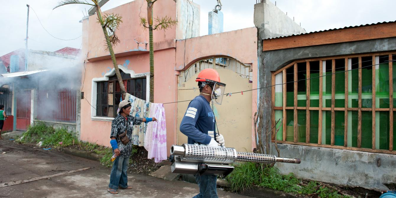 A fog machine operator works to eliminate mosquitoes in an area of Tacloban.(Photo: Eleanor Farmer/Oxfam)
