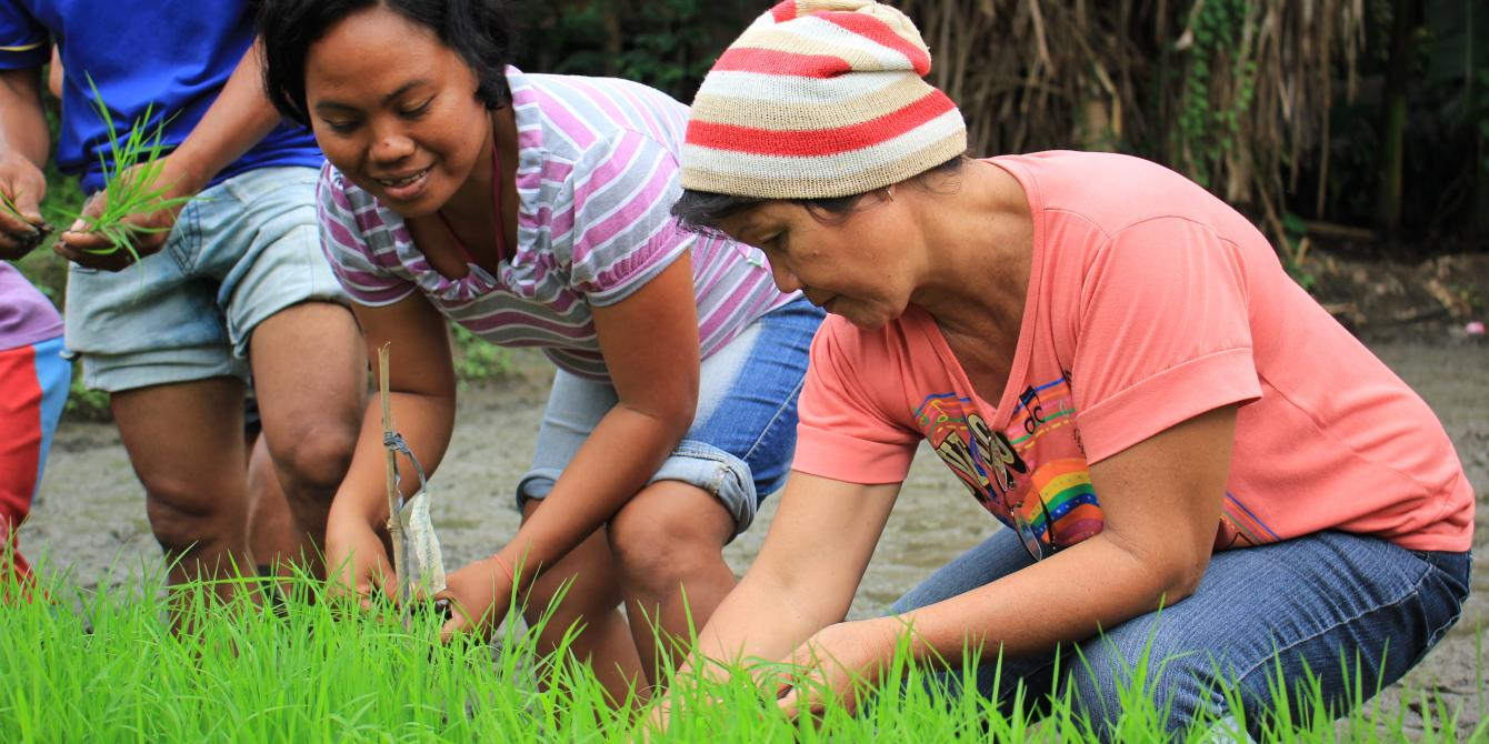 Charito, 34 years old, from Barangay Bagumbayan in Sultan Kudarat tries for the first time   precision seeding taught at the organic farming demonstration farm.(Photo: Genevive Estacaan/Oxfam)