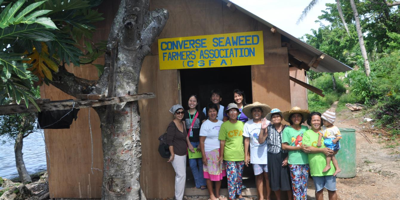 Seaweed farmers and Oxfam staff pose for a photo in front of the storage house for dried seaweeds (Photo: Maria Carolina Bello/Oxfam)