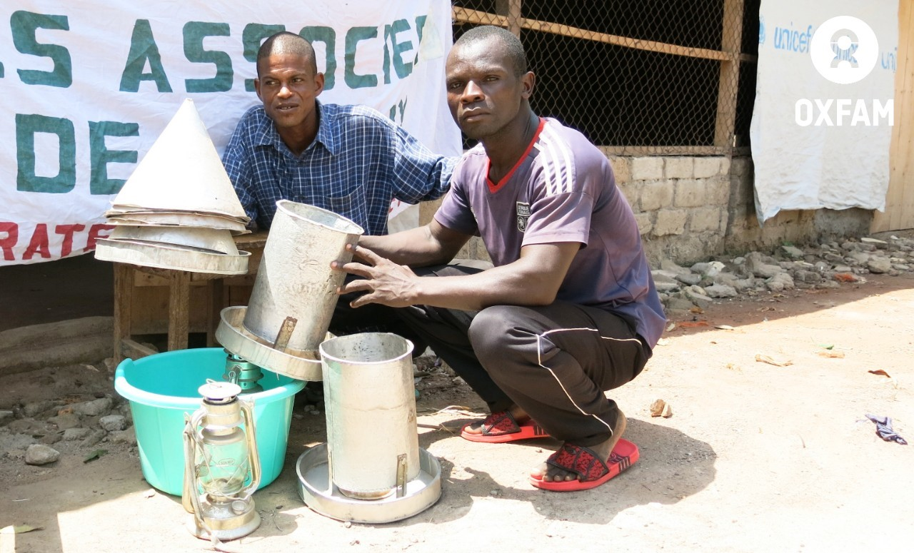 26 mars 2019-Freddy KOYAMBA et Charly KOMBOYON sortent mangeoires et abreuvoirs devant leur poulailler, dans le 5è arrondissement de Bangui. Ils font partie du groupement 'Les Associés de la paix', bénéficiaires du projet Oxfam 3x6. ©Aurélie Godet/Oxfam