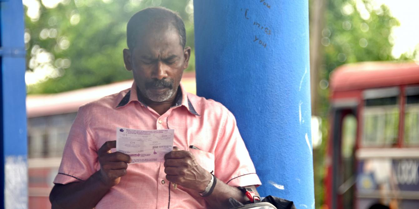 Gentleman reading a handout at the Batticoloa Bus Station. Photo credits: Sheshadri Kottearachchi