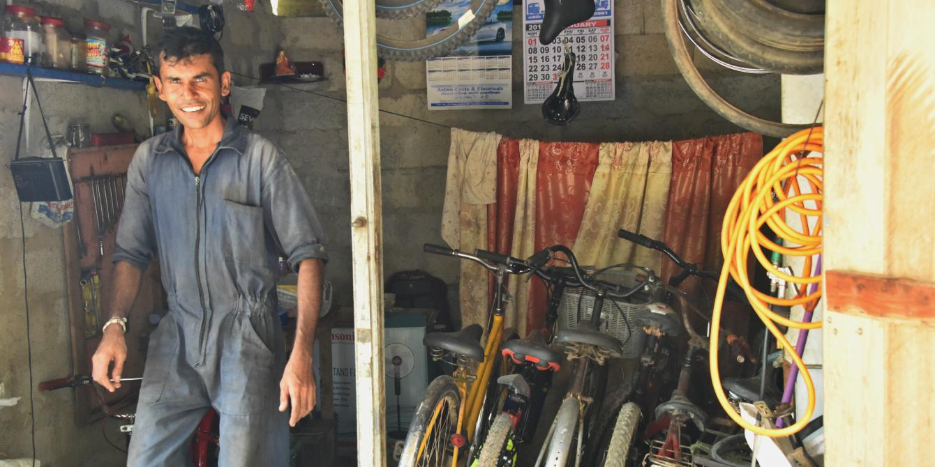 Young Sri Lanka man stands inside his repair shop
