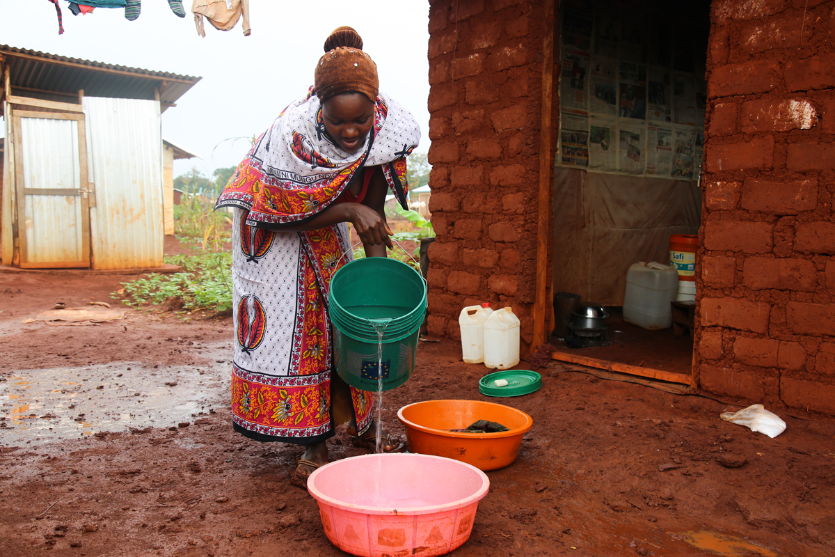 Habonimana Emerace wearing her khanga while pouring water from the kits she has received though European Commission's Civic Protection and Humanitarian Aid funding, distributed by Oxfam in Tanzania (Photo by Kisuma Mapunda).