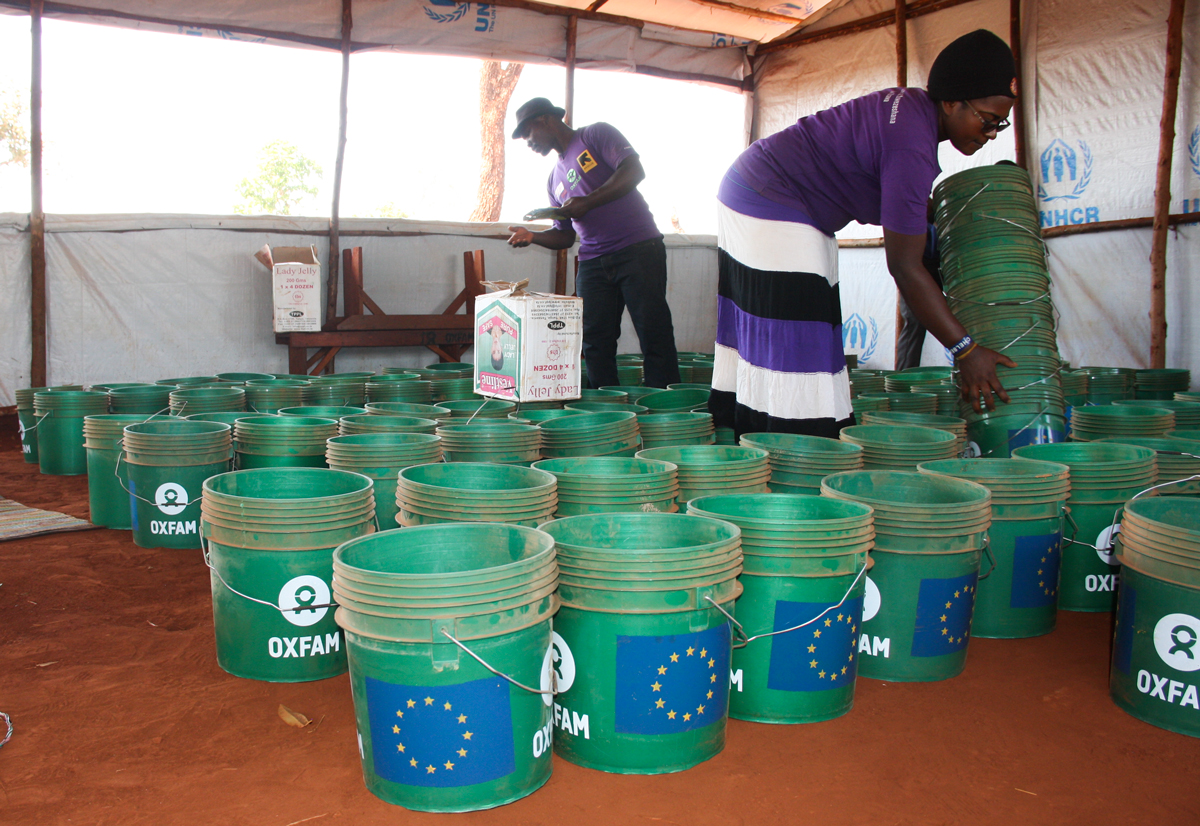 Public Health Promoters counting buckets before distributing it to the women refugees (Photo by Yussuf Kajenje)