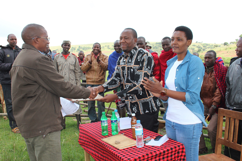 Robert Kamakia from PALISEP handing over his speech to District Commissioner of Ngorongoro, Hon. Hashim Mgandilwa. Photo: Bill Marwa/Oxfam