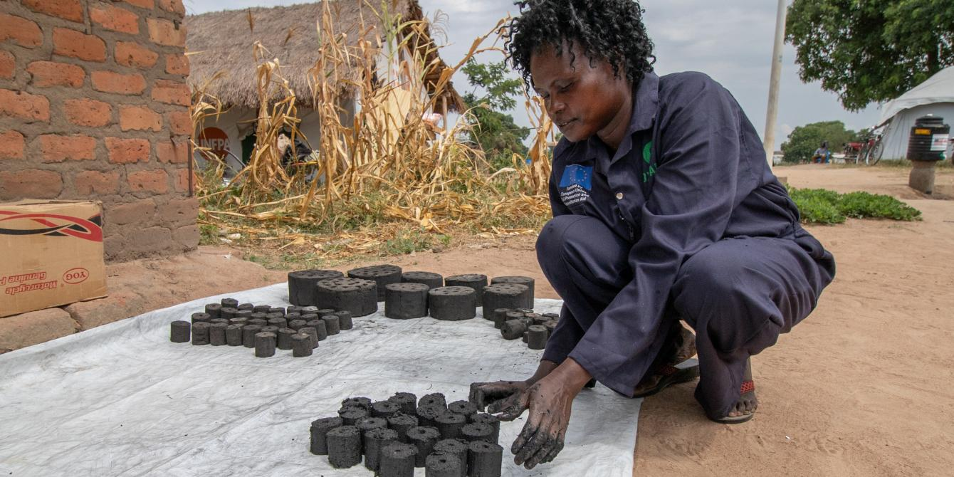 Laying out briquettes - alternatives to charcoal - to dry. Photo credit: Elizabeth Stevens/Oxfam