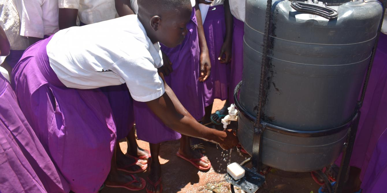 A student of Illi Primary School demonstrating proper handwashing