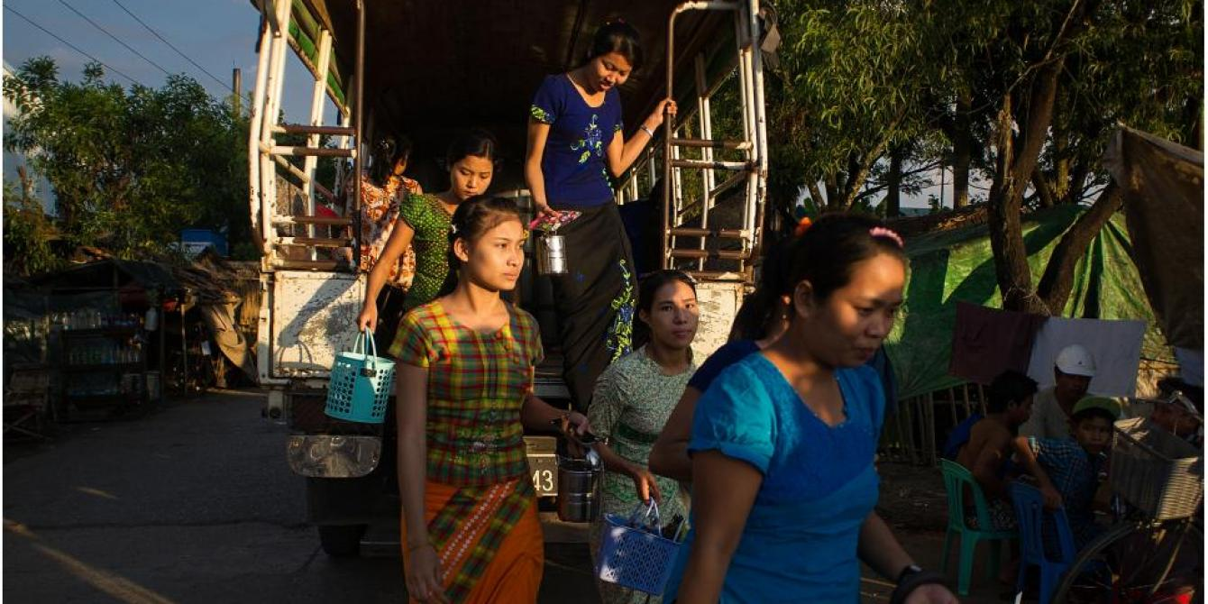 Factory workers step out of their shuttle bus as their shift ends. Hlaing Thar Yar Industrial Zone, Yangon, November 2015. Credit: Kaung Htet