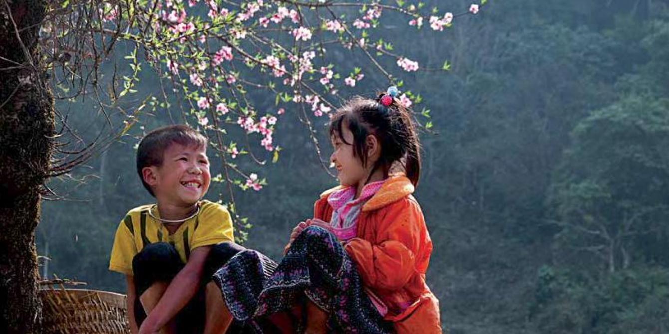 Rural children smile under peach blossoms in northern Vietnam. Credit: Oxfam Vietnam